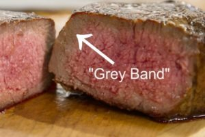 Grilled steak with overcooked grey band.
