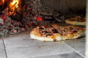 Pizza cooking in pizza oven