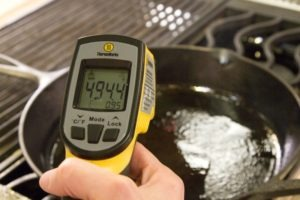 Checking the surface temperature of a cast iron pan with a ThermoWorks Infrared Thermometer.