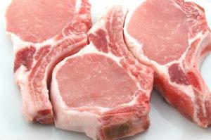three plump center cut pork chops on white