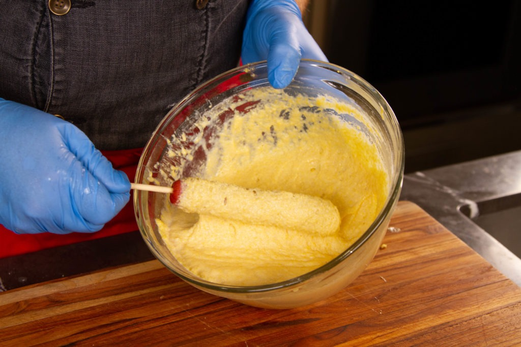 Batter the corndogs by dipping and turning them in the cornbread batter