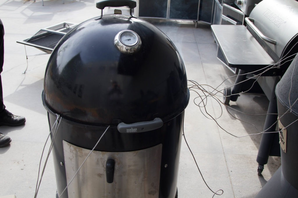 A bullet smoker with its elongated body between the heat and the meat