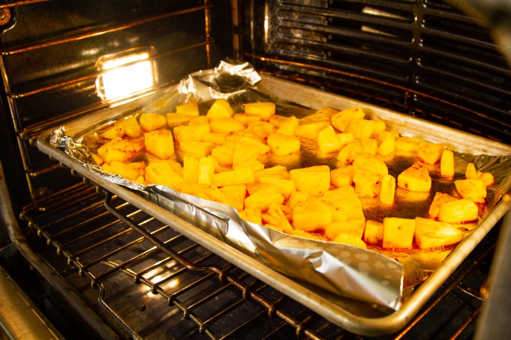 Roasting the pineapple tossed in pork fat