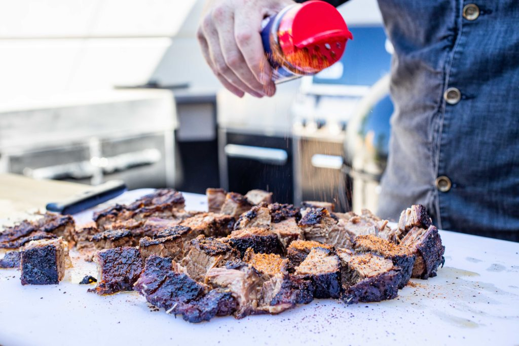 Season the cubes of brisket with rub and sauce.