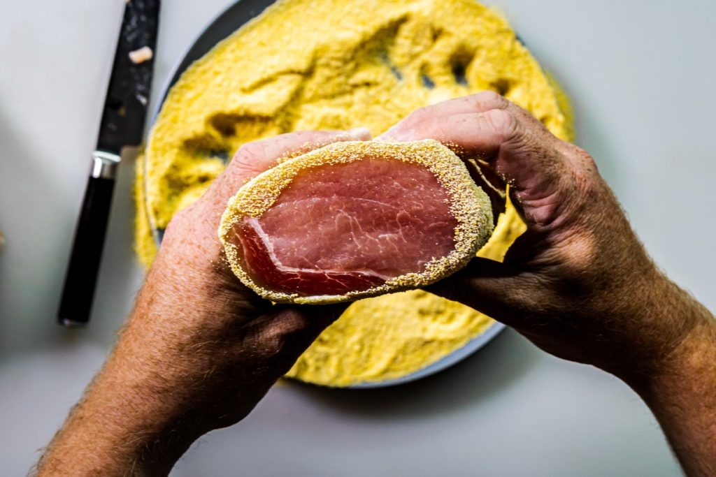 Cured pork loin rolled in corn meal: peameal bacon.