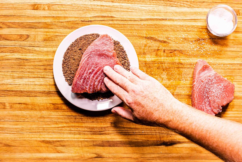 Salted tuna steaks being coated with cacao nibs