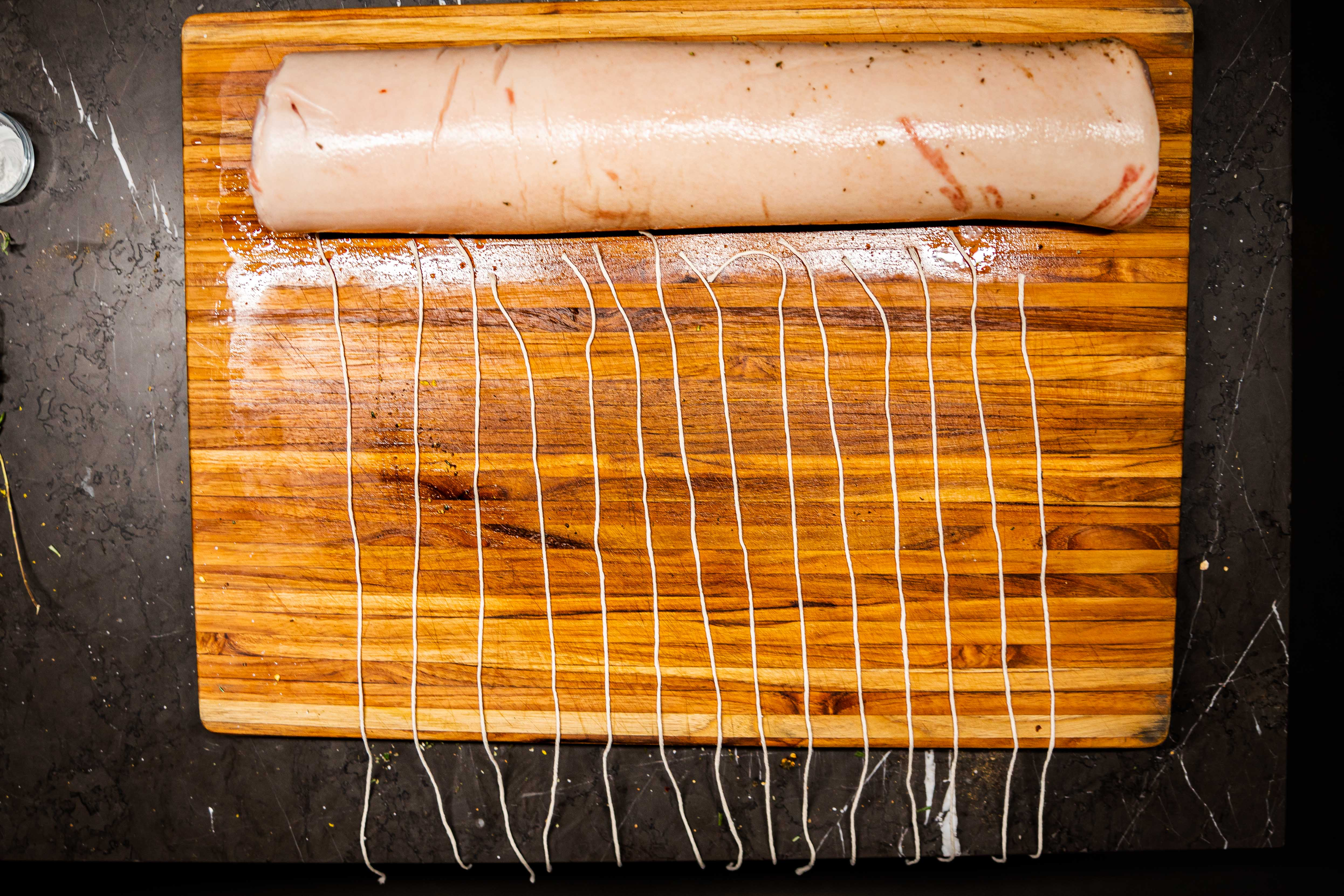 A rolled up pork belly, with twine laid out for tying it up