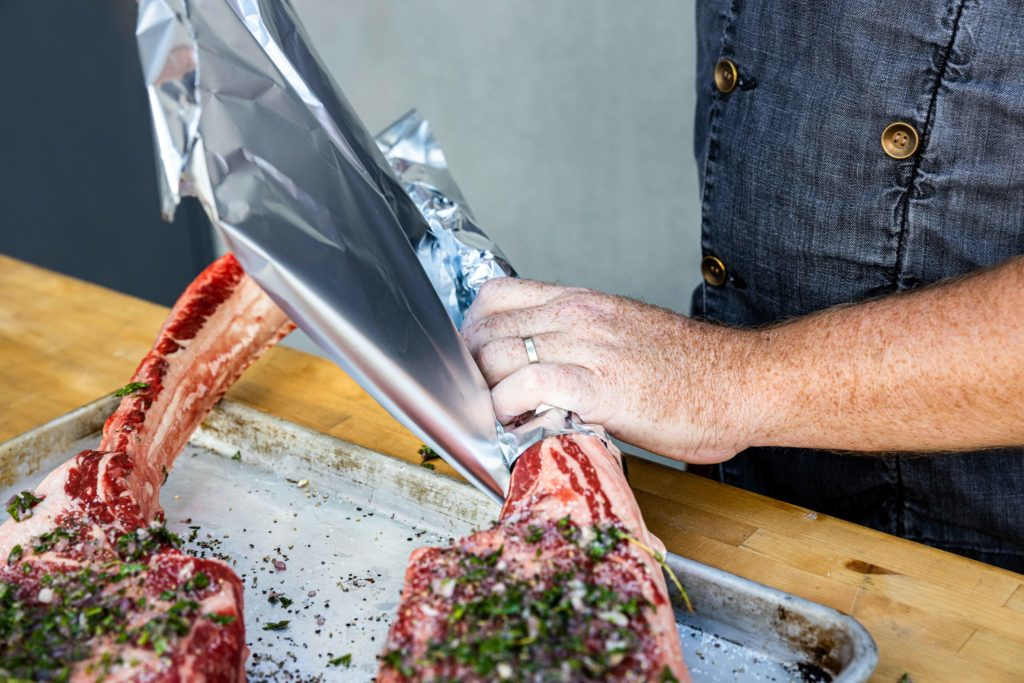 Wrapping the tomahawk steak bones in aluminum foil
