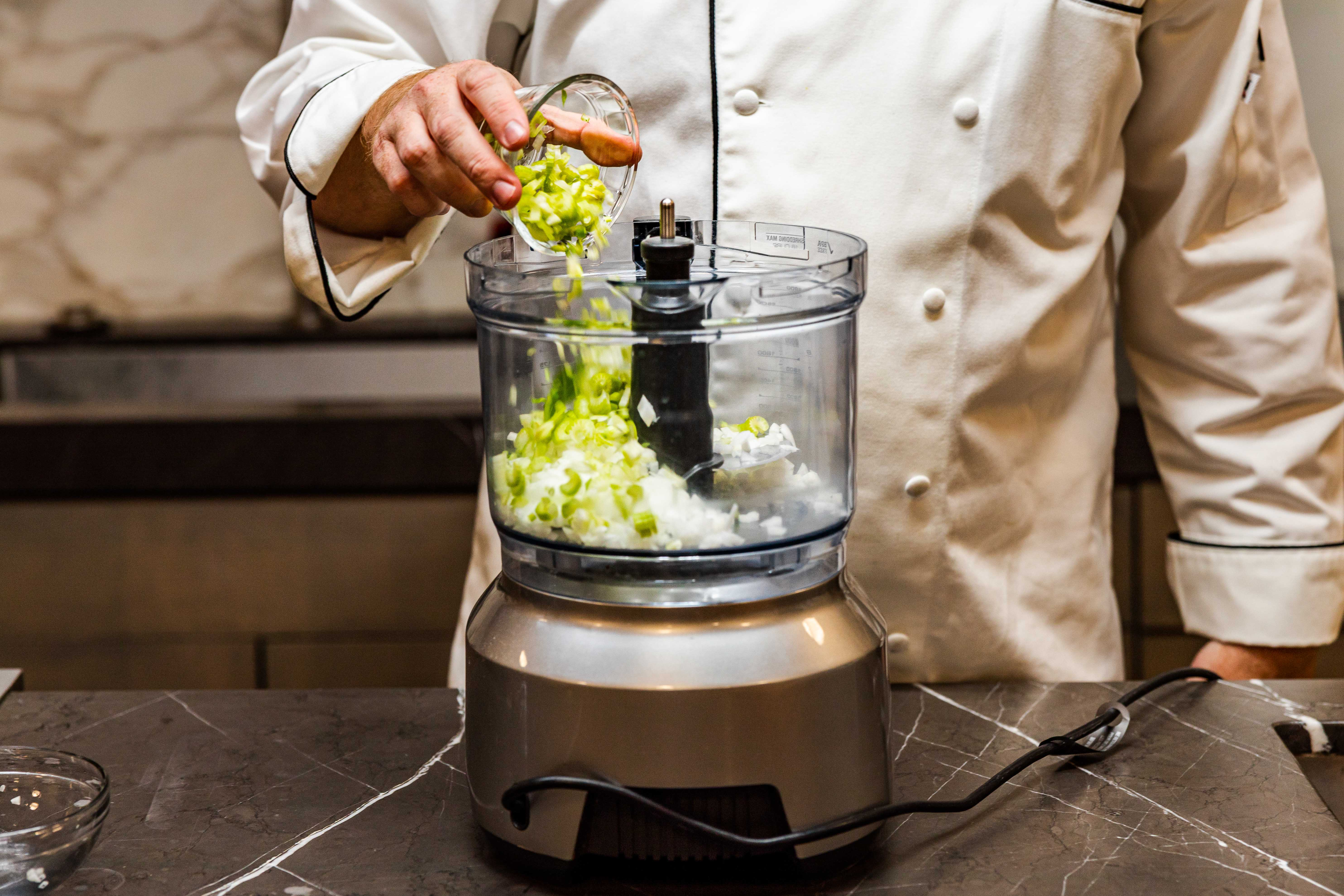 Finely chopping celery and onion in a food processor