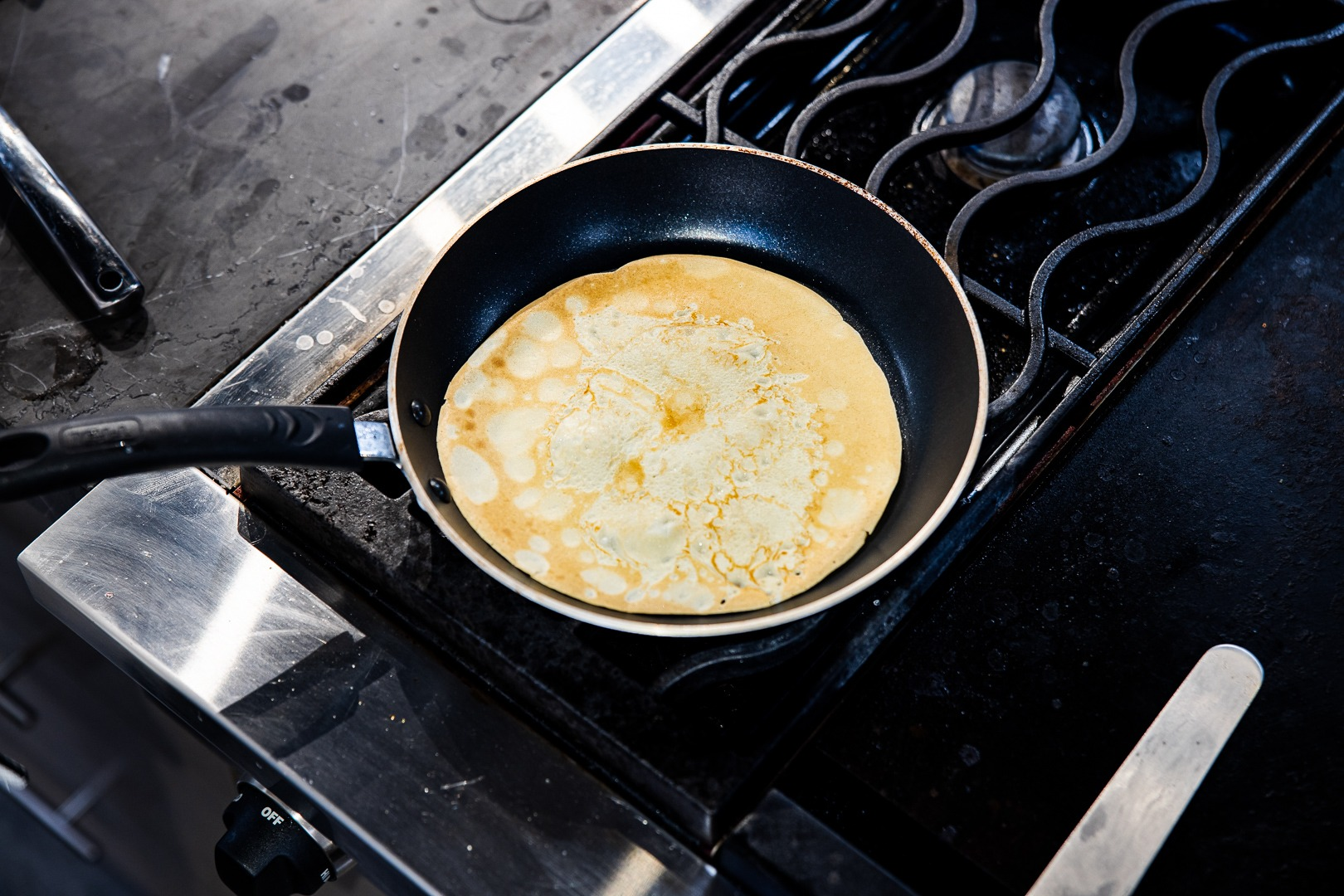 A crepe cooking on its second side