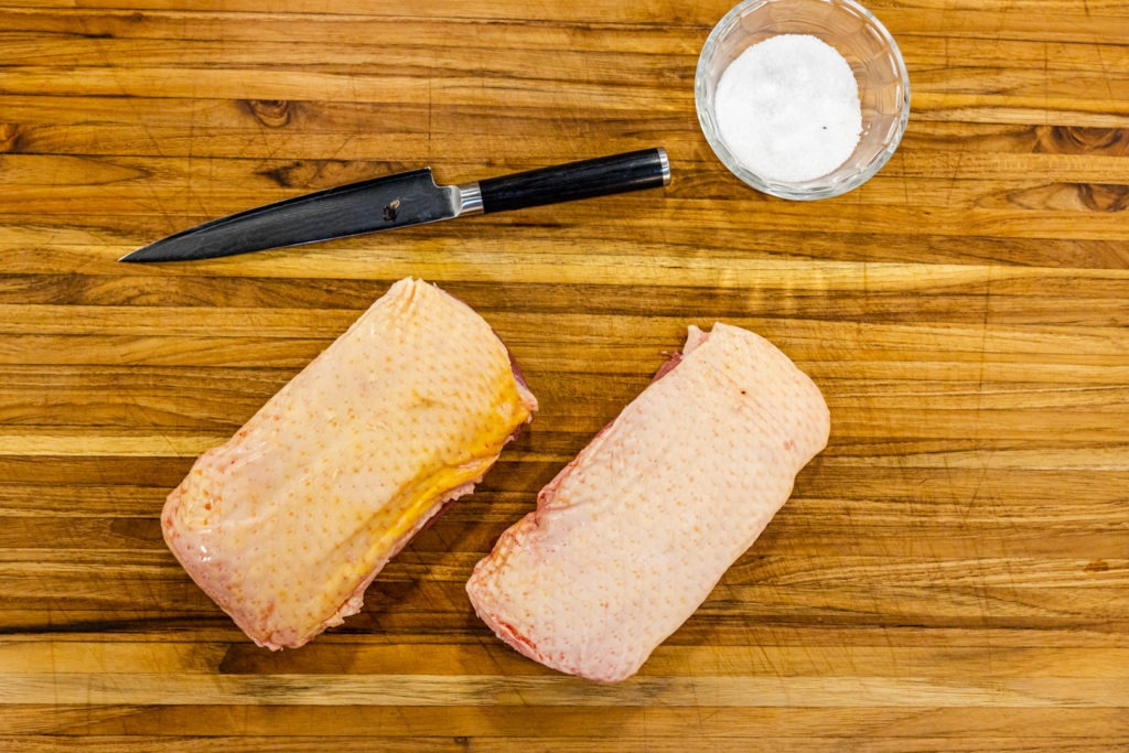 Two duck breasts, a knife, and salt for making seared duck breast.