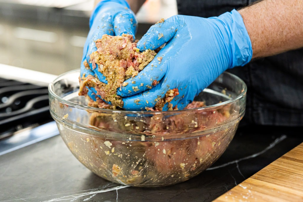 Mixing meatloaf by hand for optimal texture