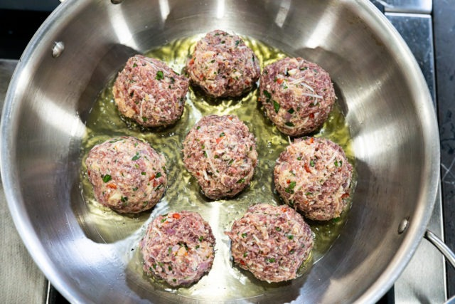 Meatballs browning on their first side in a pan