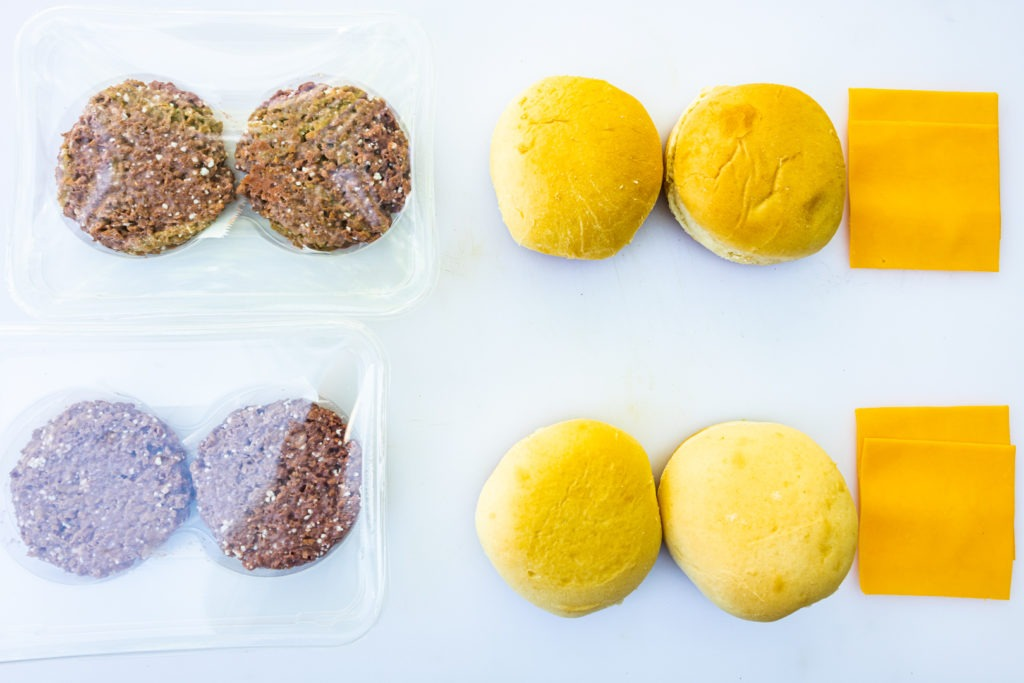 Meatless burgers, ready to be cooked alongside buns and cheese