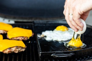 Frying eggs alongside the grilling sausage patties