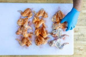 seasoning wings with BBQ rub