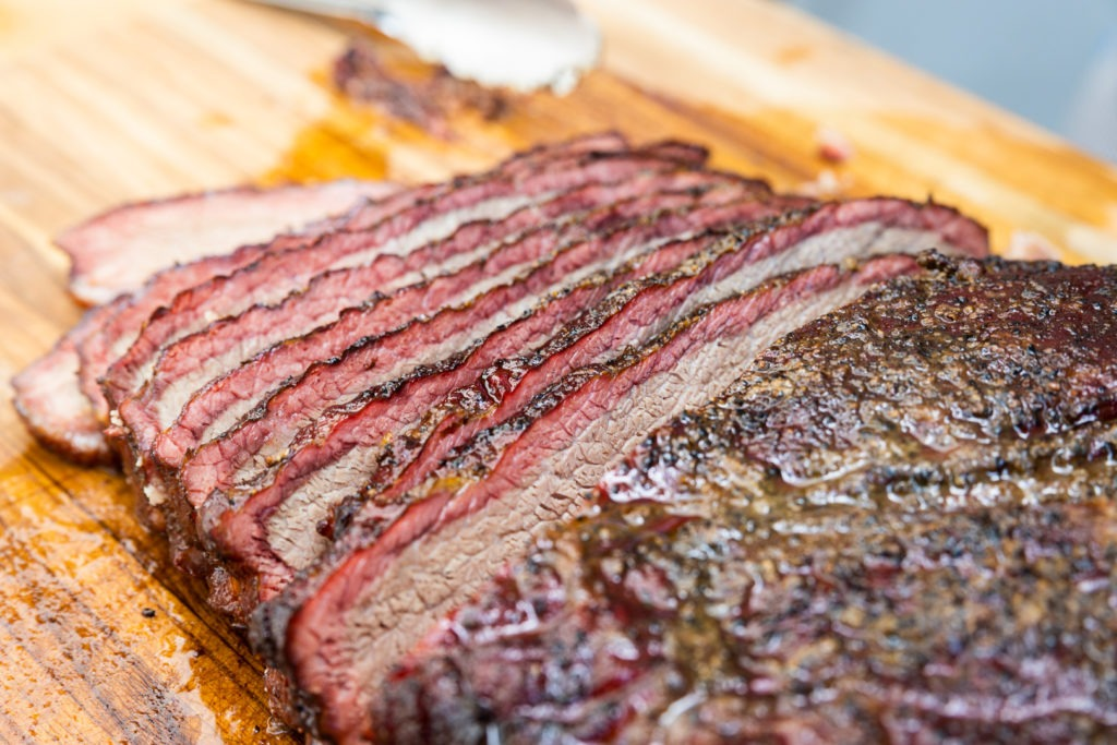 Sliced smoked brisket with a deeply-colored smoke ring