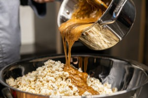 Pouring caramel onto popcorn
