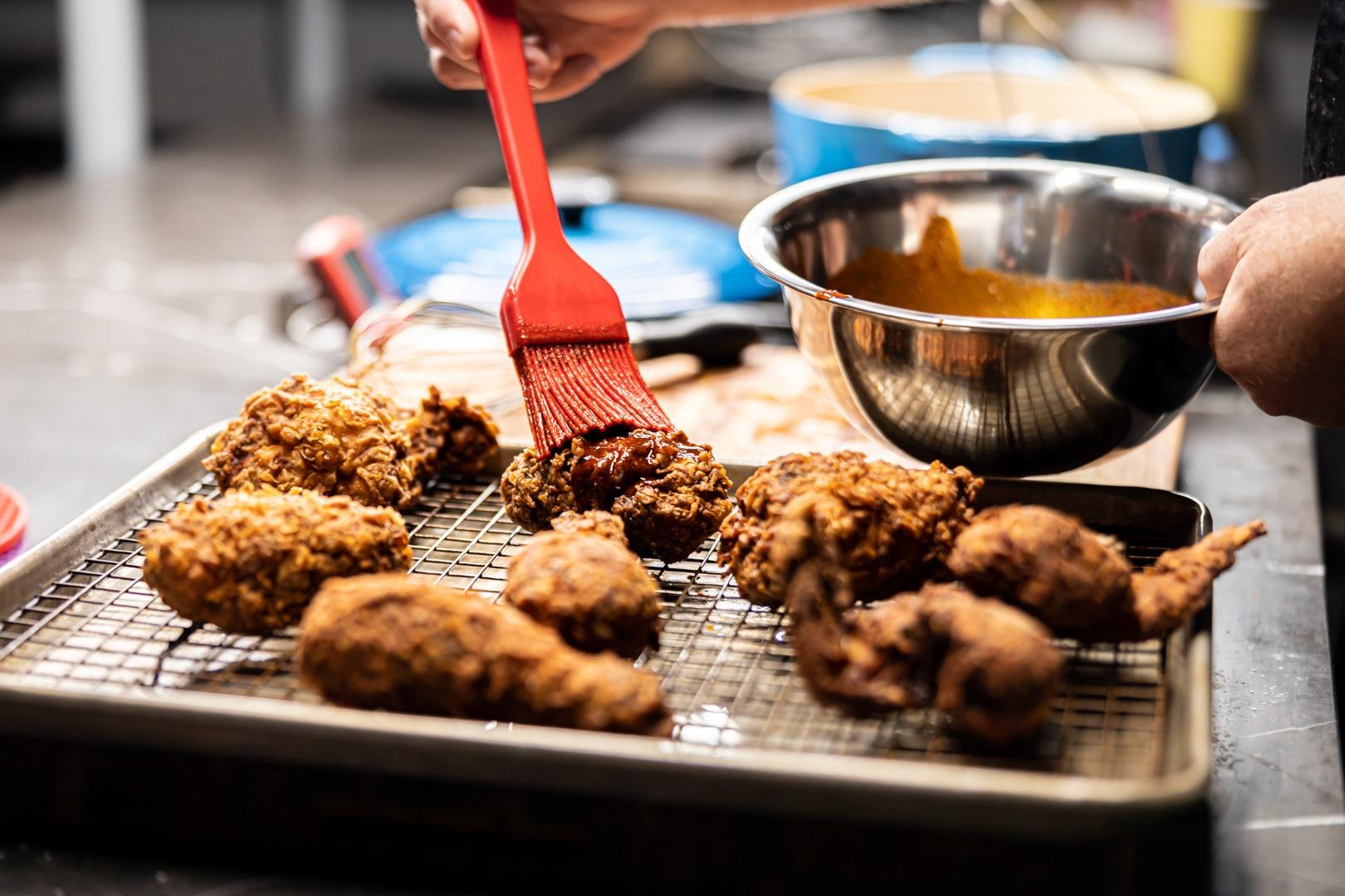 Basting chili oil onto Nashville hot chicken