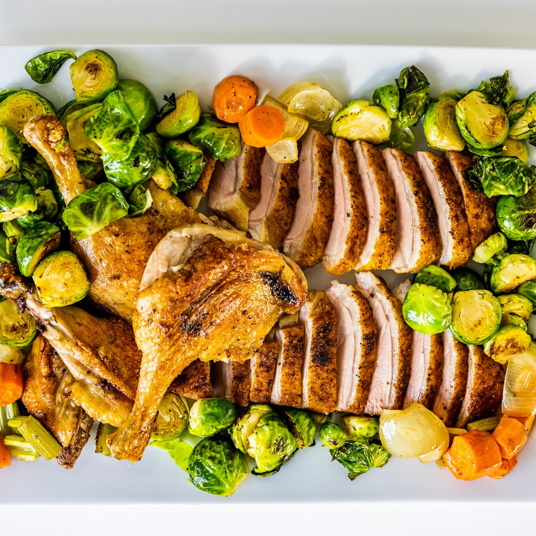 Platter of roast duck and vegetables