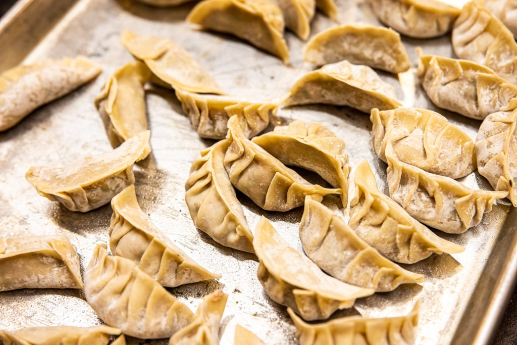 Dumplings on a sheet tray, ready to be cooked
