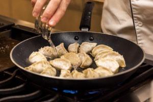 adding water to dumpling pan