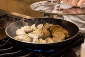 putting lid on steaming dumplings