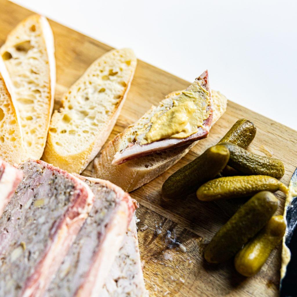 pâté de campagne with cornichon and mustard on crusty bread