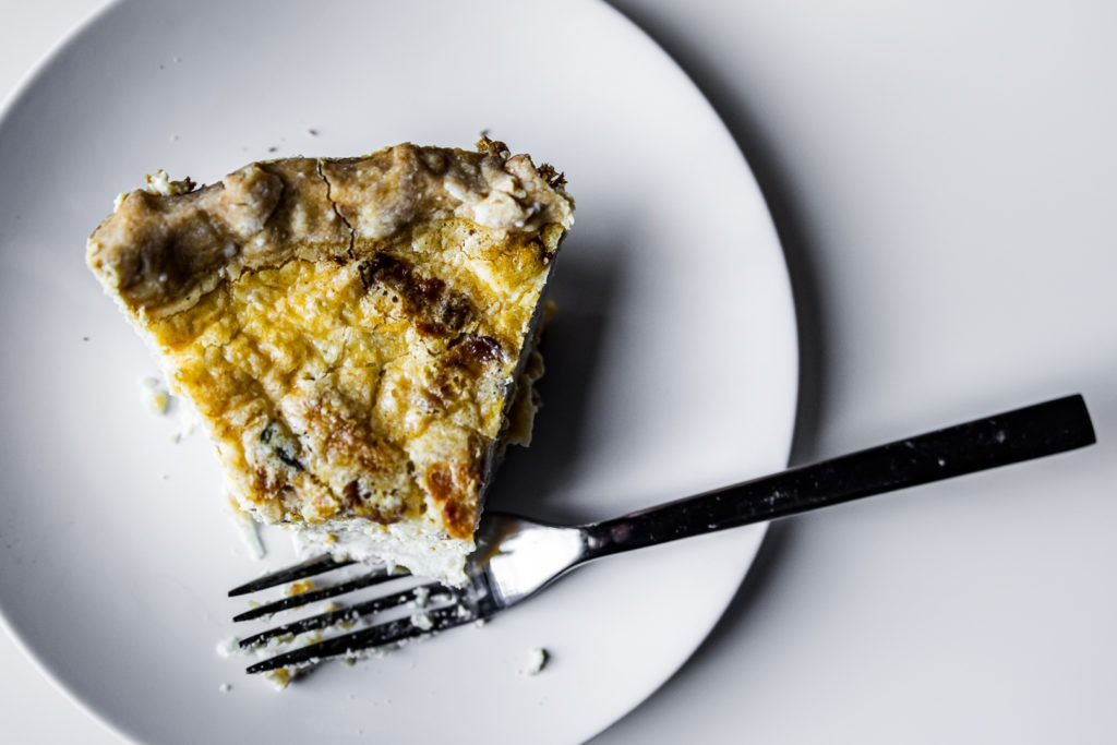 Quiche Lorraine with a bite take out, a fork, a plate