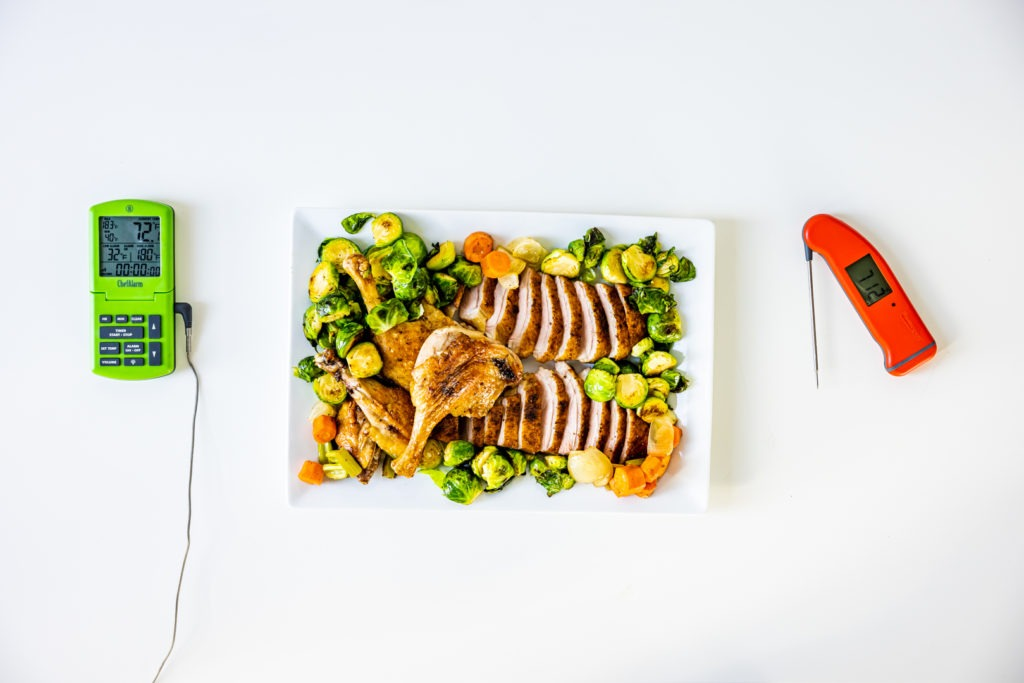 Roast duck with Brussels sprouts on a platter flanked by a ChefAlarm and  Thermapen