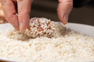 rolling the meatballs in rice