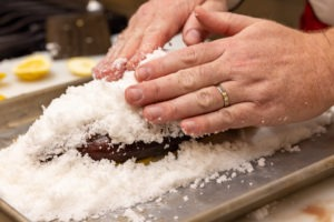 packing salt onto the fish