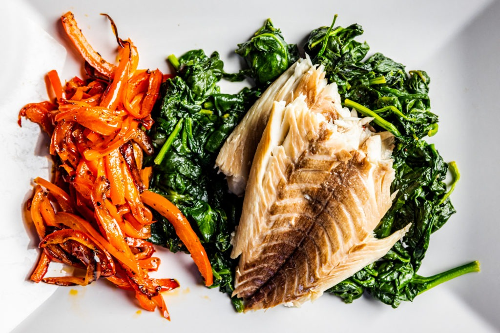 Roasted snapper served with garlic spinach and sautéed peppers