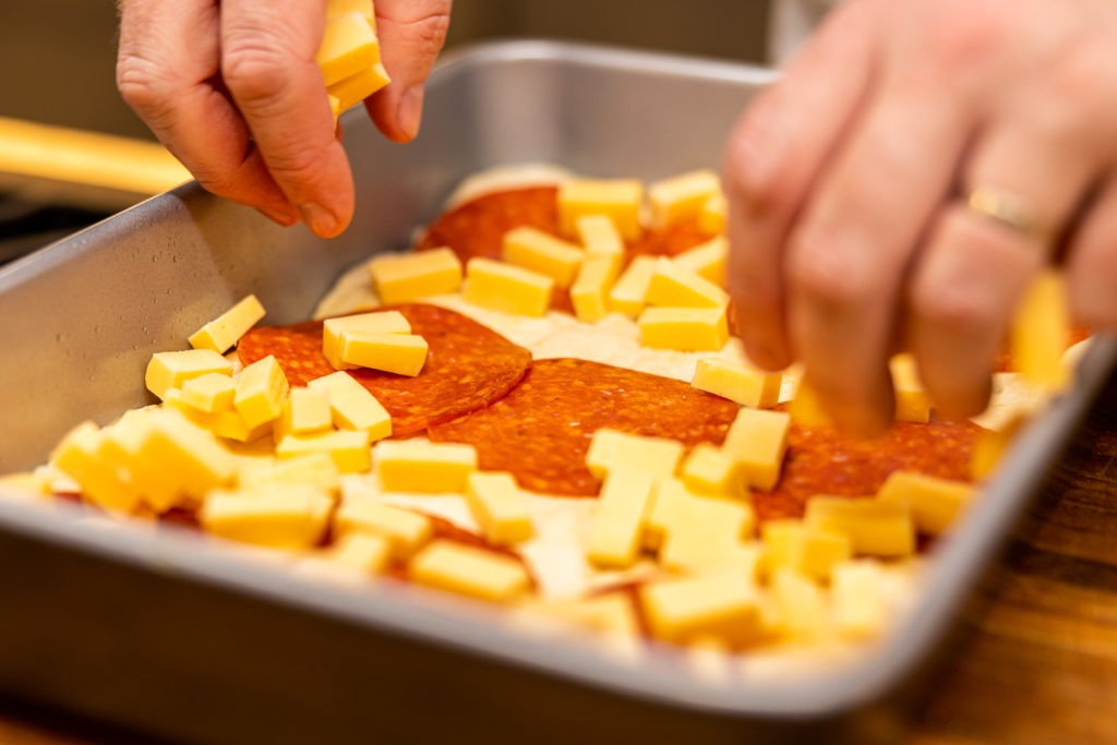 Putting cheese cubes on the pizza