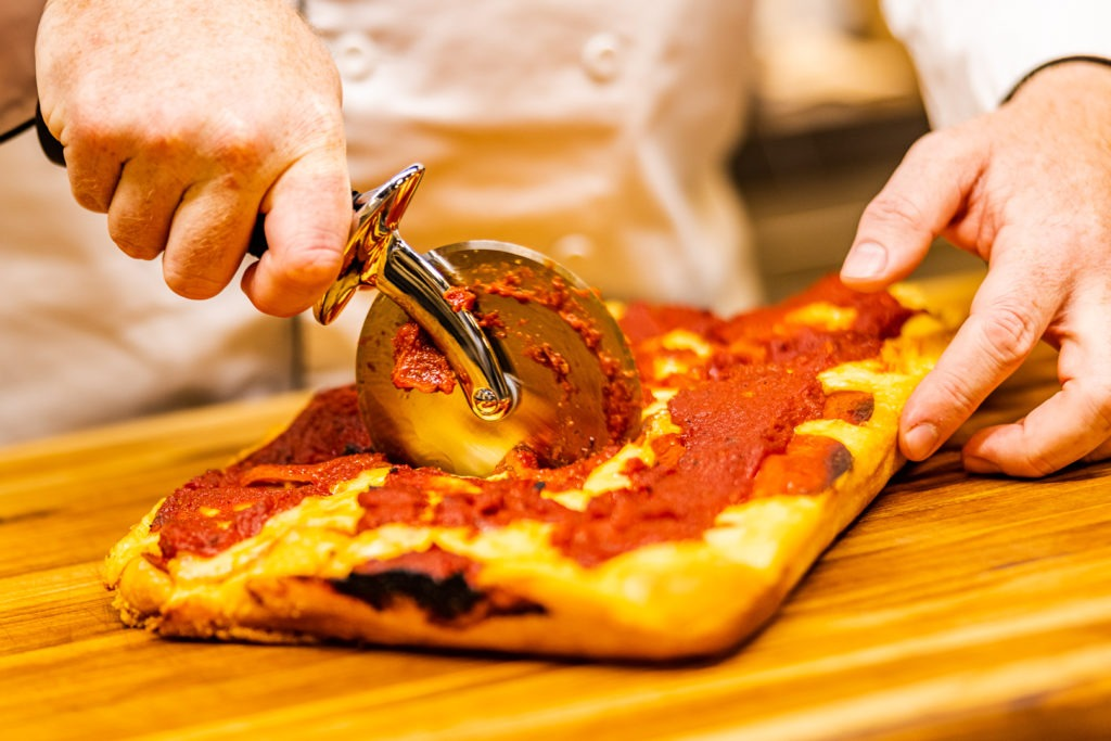 Cutting the Detroit-style pizza