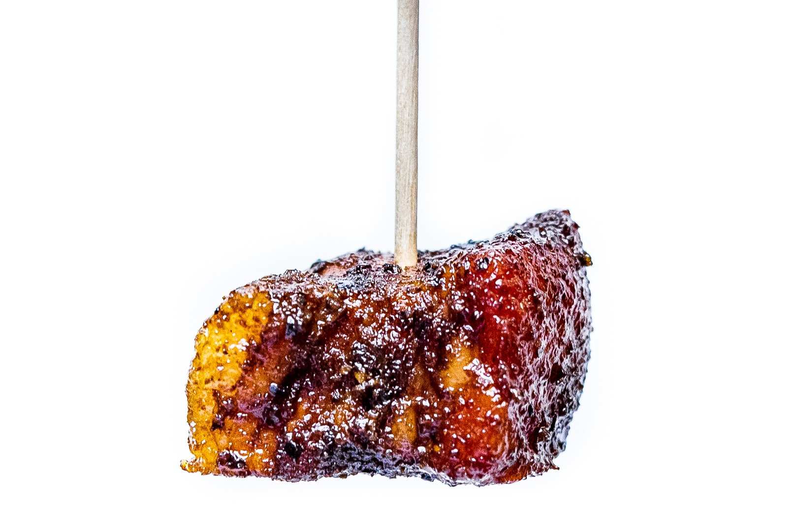 An adobo pork belly burn end on a toothpick