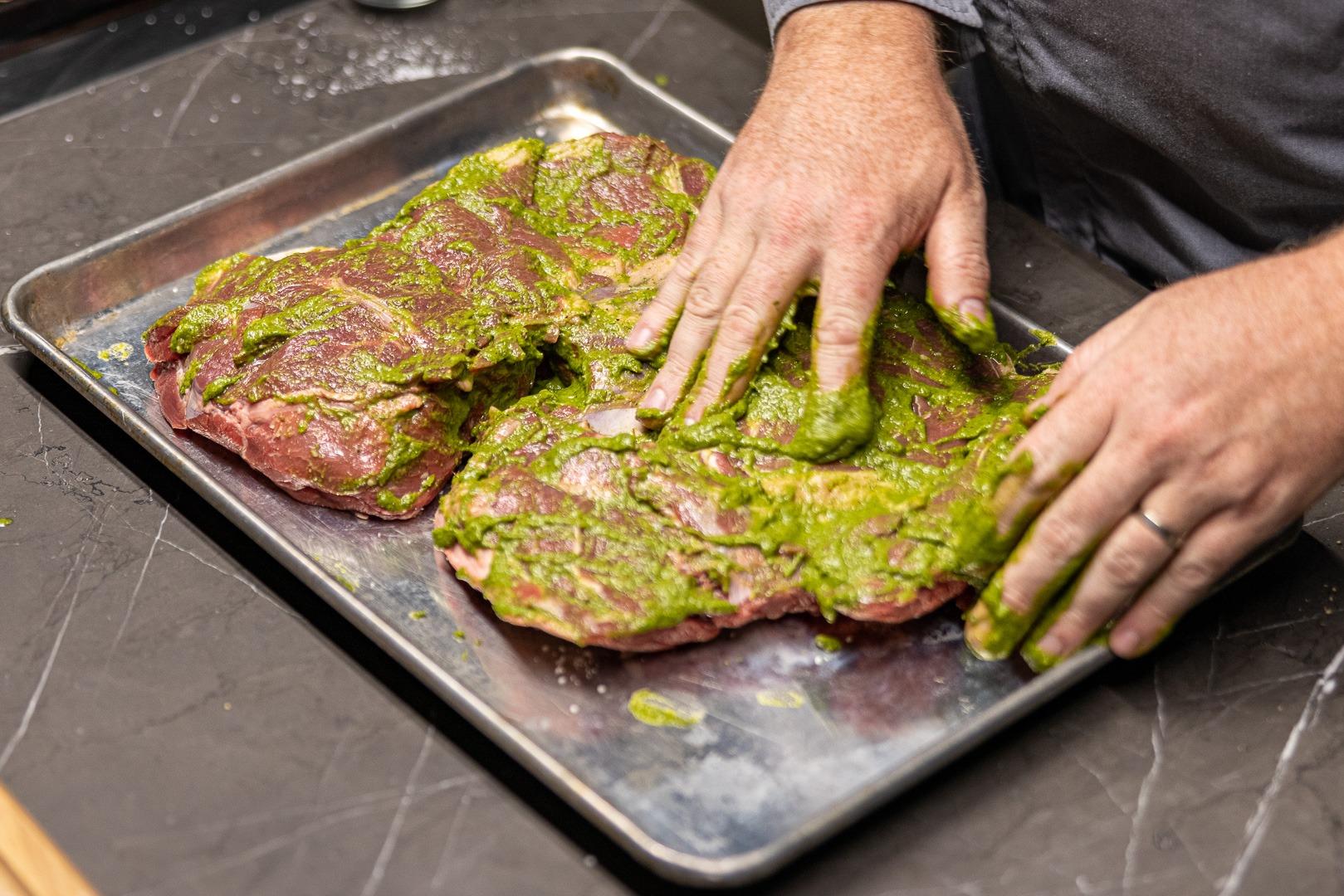 smearing the herb seasoning paste onto the leg of lamb