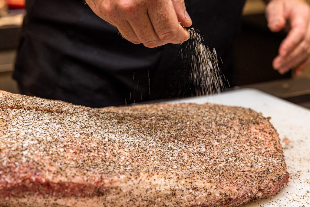 Seasoning a brisket with salt and pepper