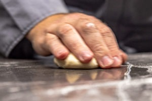 Rolling a dough ball under a cupped hand