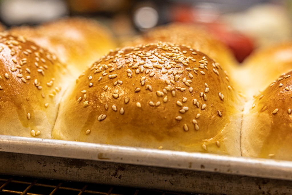 A hamburger bun, shiny and seeded and perfect