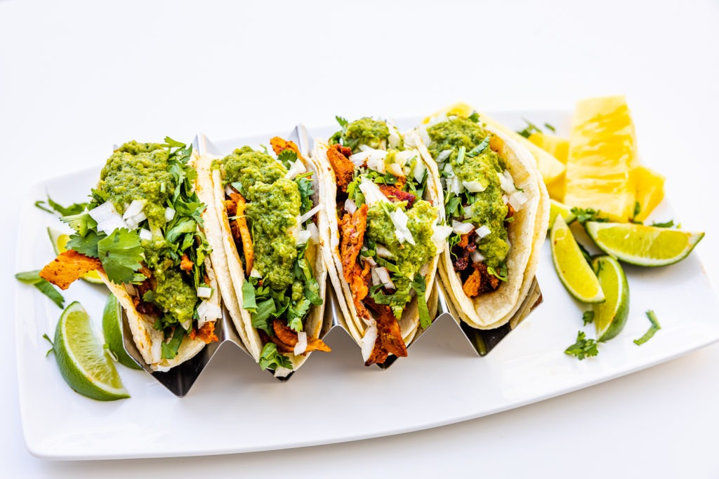 tacos al pastor with lime wedges and pineapple slices