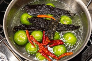 Tomatillos and chiles in boiling water