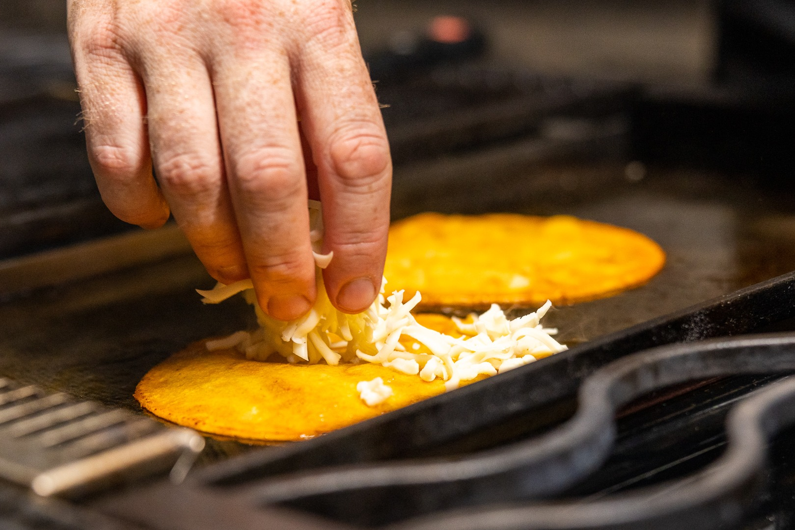 adding cheese to the quesabirria