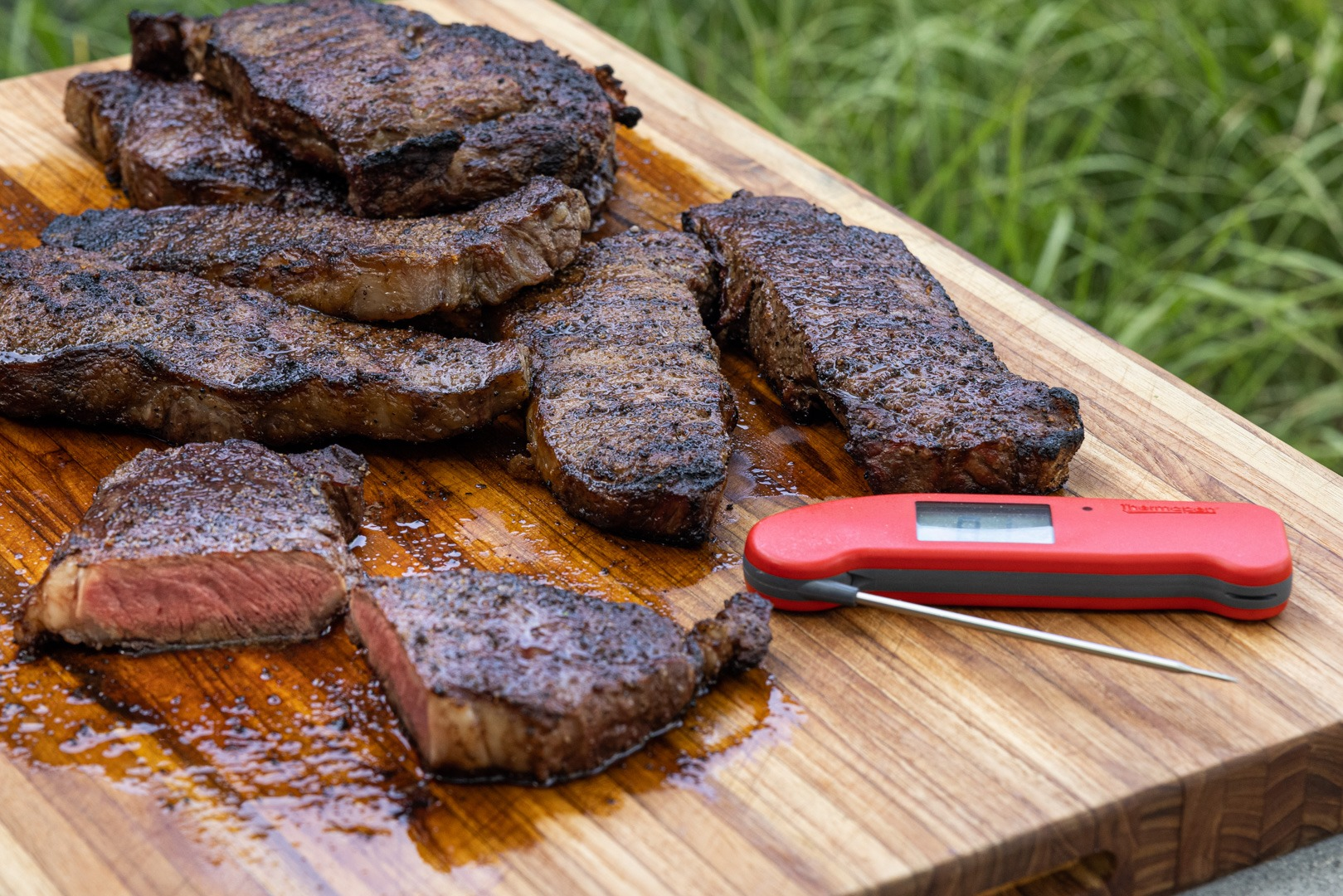 A board of cooked steaks with a Thermapen ONE