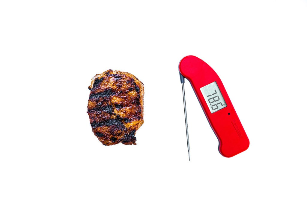 A grilled pork chop with a Thermapen