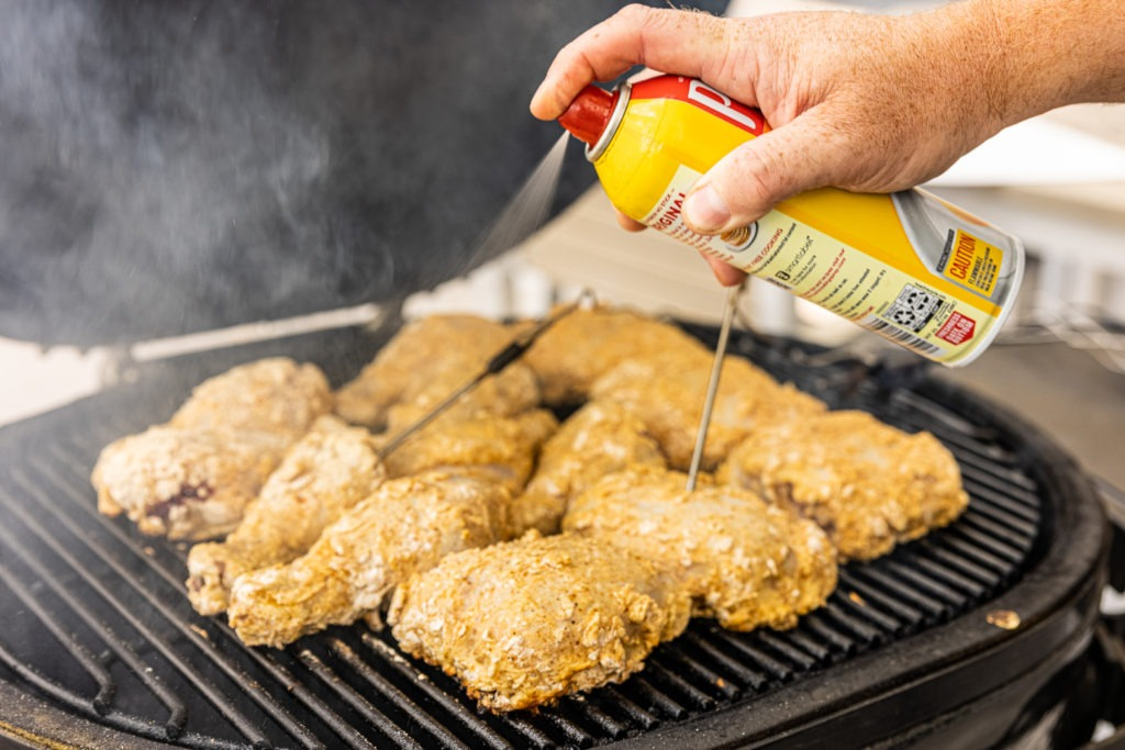 Spraying chicken with cooking spray to help it air fry
