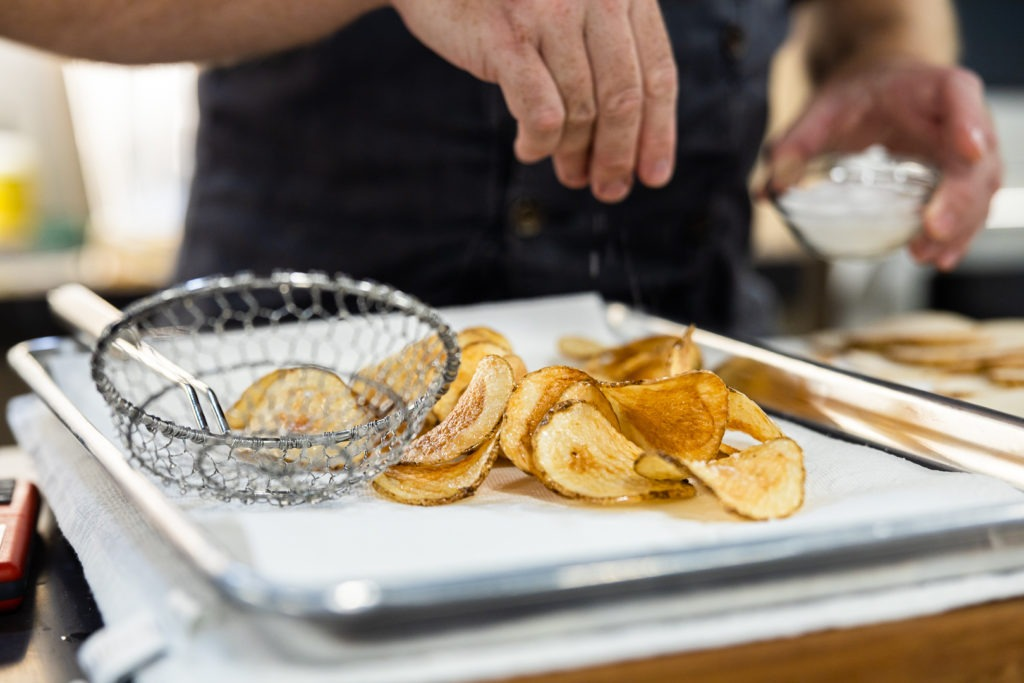Homemade kettle chips draining on paper towels