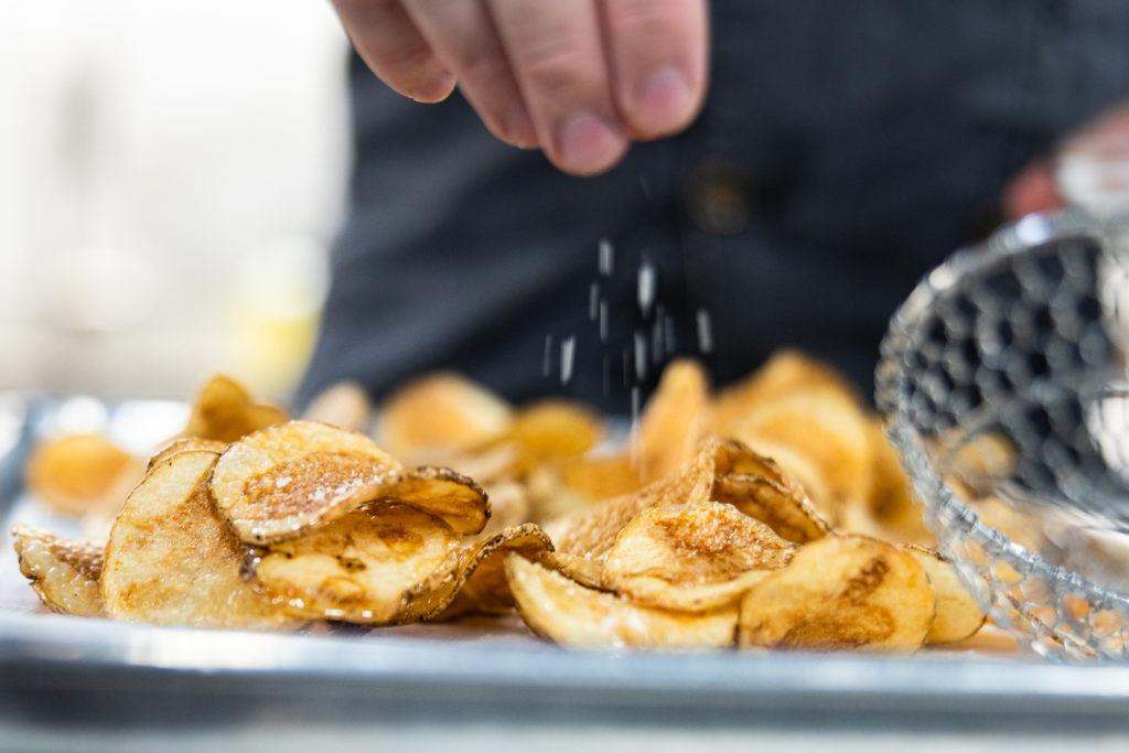 Salting homemade potato chips