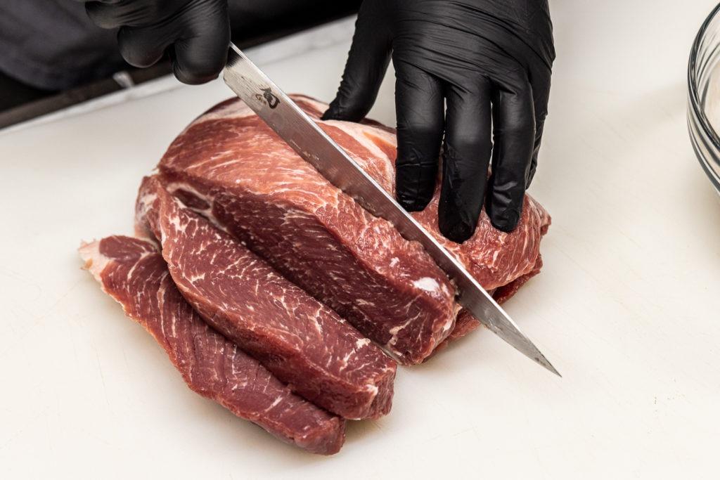 Slicing pork shoulder for tasso