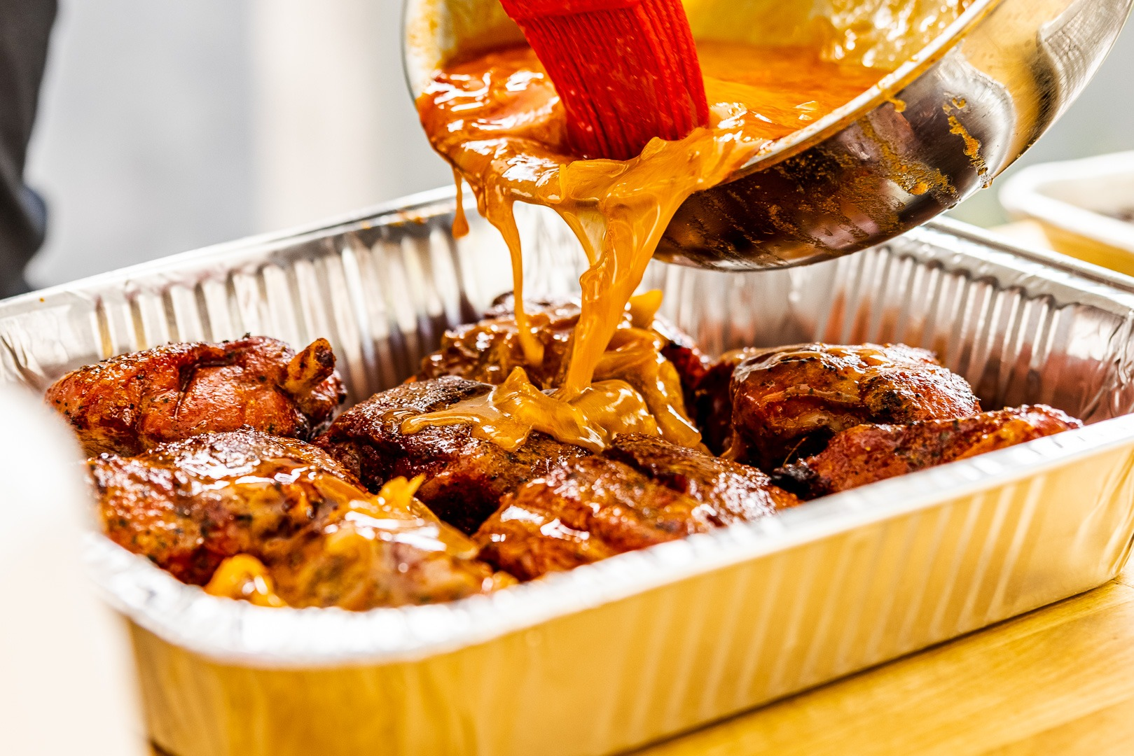 pouring sauce onto wings in pan